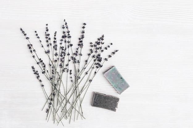 Barras de sabão artesanal com ingredientes orgânicos naturais, flores de lavanda secas na mesa de madeira branca