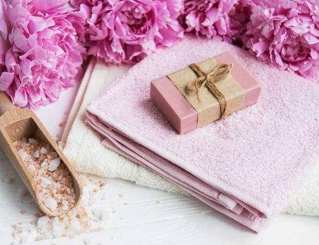 Barras de sabonete artesanal, toalhas macias e flores de peônia