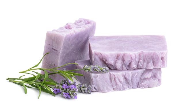 Barras de sabonete natural de lavanda caseira com flores de lavanda isoladas no fundo branco.