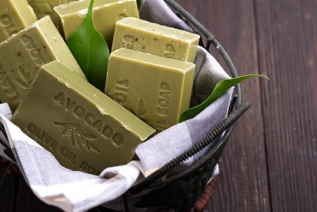 Barras de sabonetes de azeite verde natural com folhas verdes em uma cesta no escuro de madeira