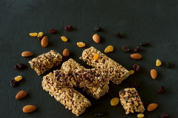 Barras energéticas de granola caseira com amêndoas e passas em fundo preto. comida saudável.