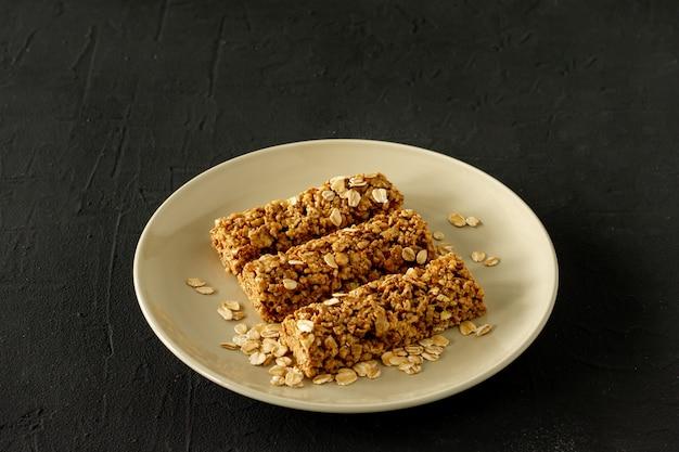 Barras energéticas de granola caseira com amêndoas e passas no alimento saudável preto.