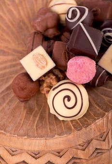 Barras quebradas de chocolate ao leite com nozes, frutas sublimadas e bombons de chocolate em fundo de madeira rústico, com espaço em branco para vista superior do texto, plano leigo