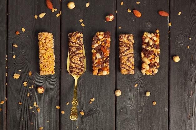 Barras saudáveis com nozes, sementes e frutas secas na mesa de madeira