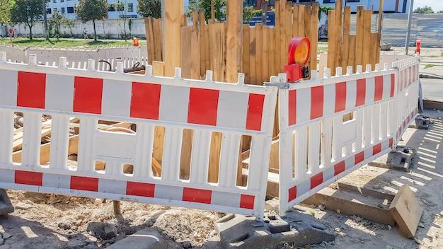 Barreira protetora de plástico cerca o local da obra rodoviária. cerca de plástico vermelha e branca perto do local de reparo da rua. obras de construção na rua, reparação de estradas, cerca protetora.