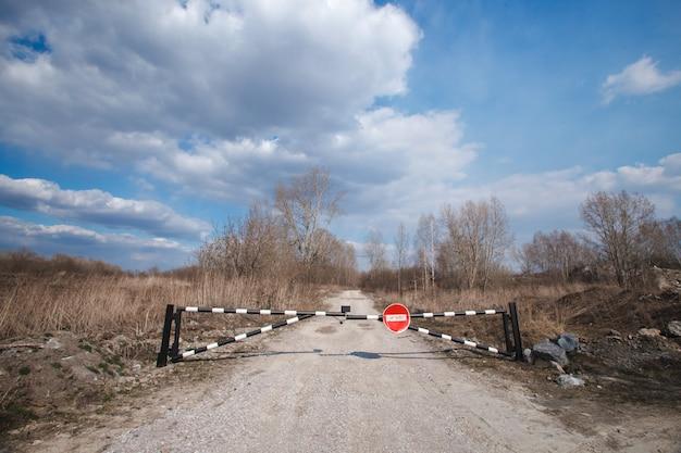Barreira sem sinal da entrada, faixa verde e floresta