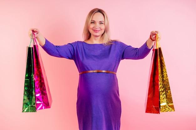 Barriga de bebê grande bonita loira sorridente mulher grávida segurando sacolas de compras no estúdio em um fundo rosa. comprando roupas para grávidas conceito