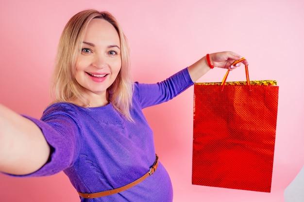 Barriga de grande bebê linda loira sorridente mulher grávida segurando sacolas de compras ee faz selfie telefone no estúdio em um fundo rosa. conceito de shopaholicism