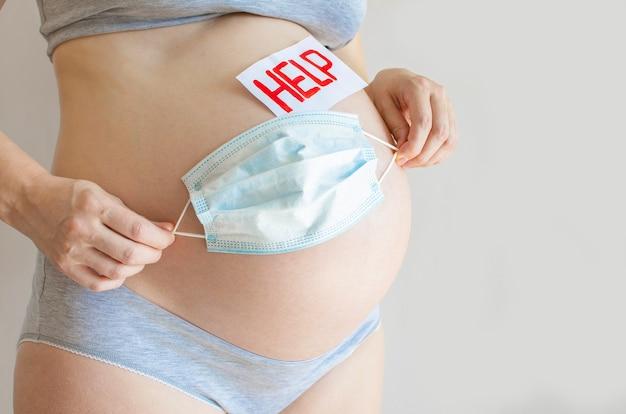 Barriga de grávida com máscara de proteção médica e sinal de ajuda