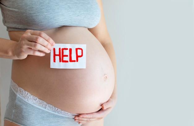 Barriga de grávida com um texto de ajuda.