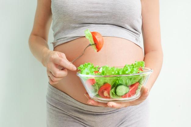 Barriga de mulher grávida e salada de legumes