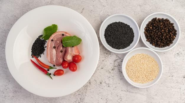 Barriga de porco cortada em um prato branco com sementes de pimenta e tomate.