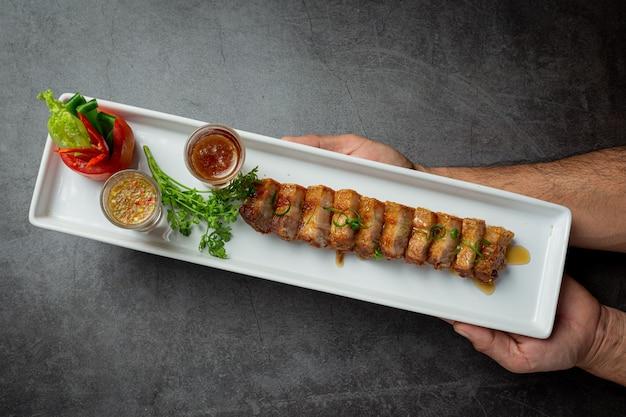 Barriga de porco frita com molho de peixe em fundo escuro
