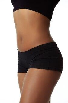 Barriga e quadris. corpo magro de mulher bronzeada isolado na parede branca.