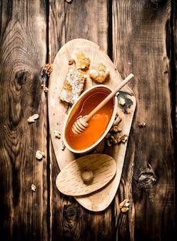 Barril com mel e nozes em tronco de árvore com fundo de madeira