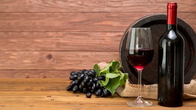 Barril de madeira com garrafa e copo de vinho