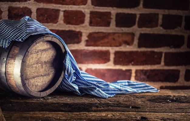 Barril de madeira da oktoberfest e toalha de mesa azul na mesa de carvalho rústica.