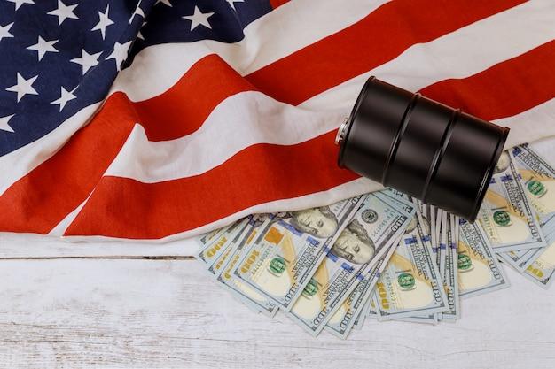 Barril de petróleo e preços de notas de cem dólares em um fundo de bandeira americana