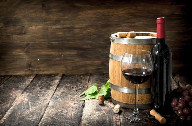 Barril de vinho tinto com uvas e um saca-rolhas. sobre um fundo de madeira.