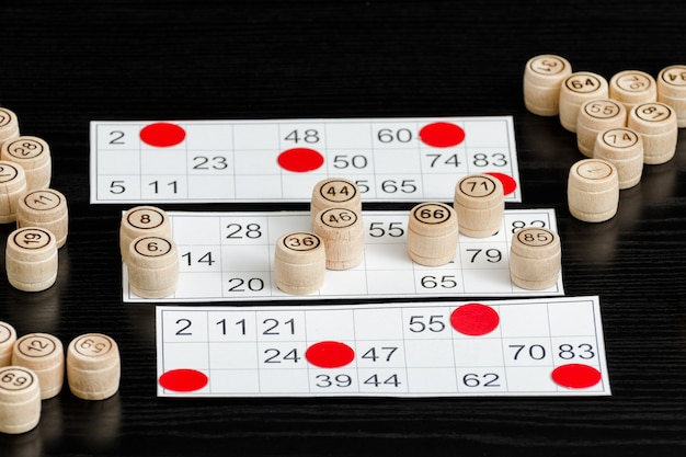 Barris de loteria de madeira, cartas e fichas para jogar em uma mesa preta