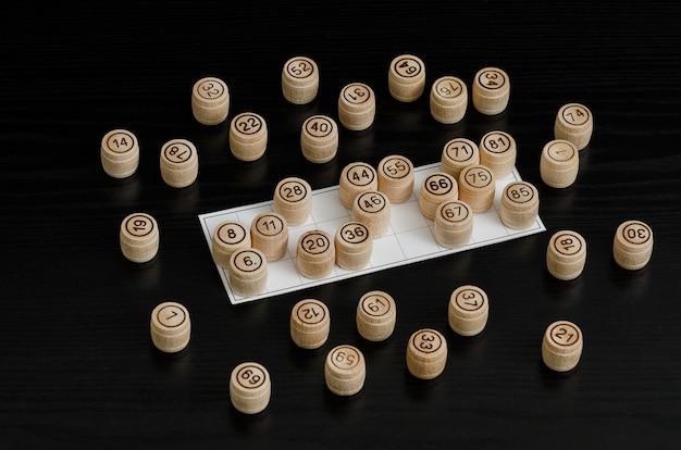 Barris de loteria de madeira e cartão para jogar em uma mesa preta