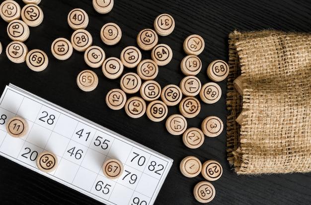 Barris de madeira da loteria, cartão para o jogo e saco em uma tabela preta. diretamente acima.