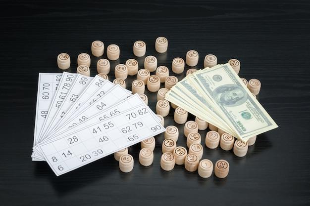 Barris de madeira loteria, cartões e dólares. mesa de madeira preta.