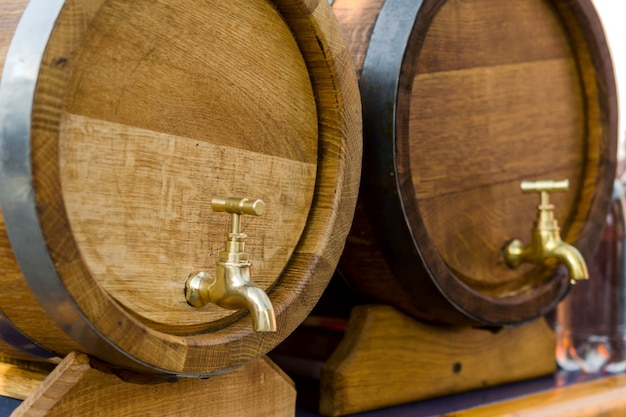 Barris de madeira para vinho com uma torneira de metal amarelo.