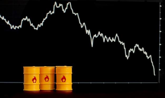 Barris de petróleo e gasolina no fundo de uma tela com um gráfico de queda