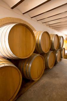 Barris de vinho de madeira de carvalho empilhados em uma fileira na adega