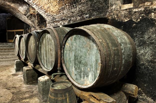 Barris velhos do barril na fileira na adega de vinho velha