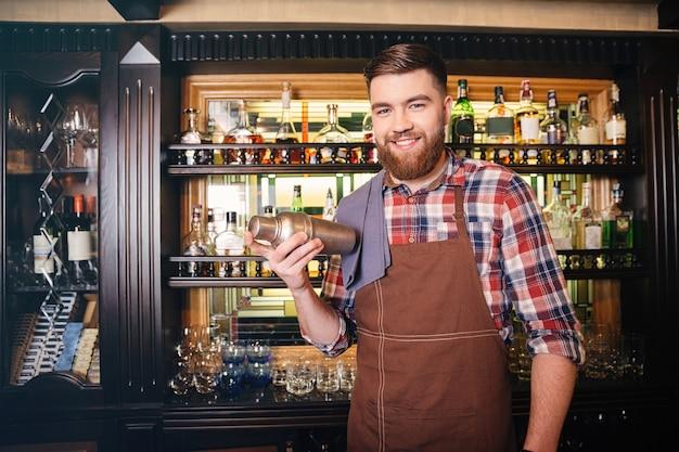 Bartender bonito e feliz com avental marrom em pé e segurando uma coqueteleira no bar
