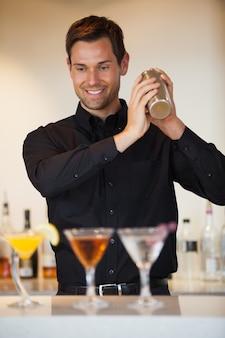 Bartender feliz sacudindo cocktails