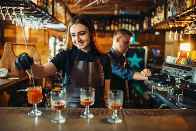 Bartender masculino e feminino no balcão do bar
