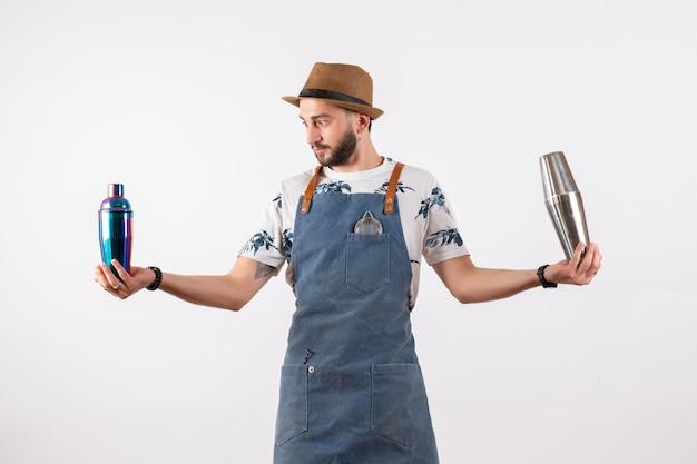 Bartender masculino segurando coquetéis na parede branca de bar de bebidas alcoólicas em modelo de trabalho noturno de bar de bebidas alcoólicas