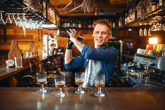 Bartender trabalha com shaker no balcão do bar