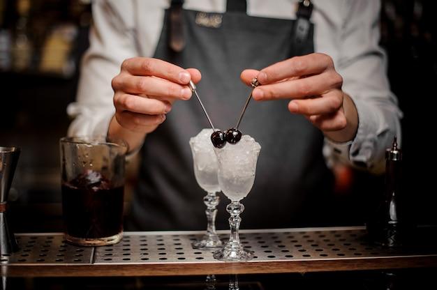 Bartman mãos decorando dois copos de cocktail com cerejas