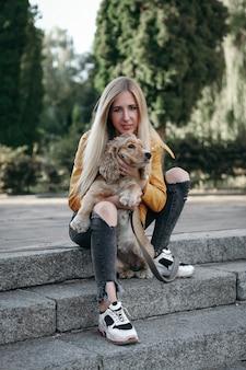 Barulho e estilo vintage. jovem com cachorro passeios no parque e goza o lindo dia de verão.