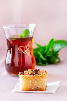 Basbousa ou namoora tradicional sobremesa árabe e chá de menta. bolo de semolina caseiro delicioso. copie spase. foco seletivo.