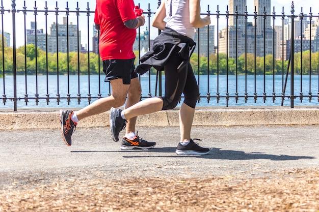 Basculador correndo ao longo do reservatório do central park, em nova york. o central park está cheio de pessoas ativas durante todo o ano.