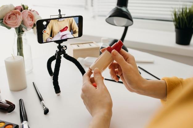 Base de maquiagem de streaming do blogger online com smartphone