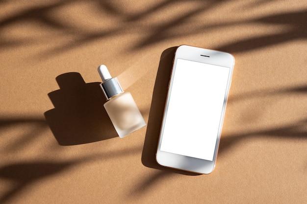 Base de maquiagem líquida em frasco de vidro e simulação de telefone celular em fundo marrom com sombras escuras, conceito de natureza morta moderna vista superior