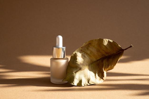 Base de maquiagem líquida em frasco de vidro em fundo marrom com sombras escuras, natureza morta moderna e simulação de vista lateral do conceito