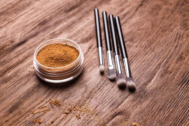 Base de pó mineral com pincéis sobre superfície de madeira. produtos de beleza ecológicos e orgânicos