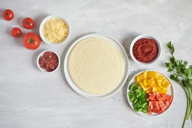 Base e ingredientes de pizza de massa fresca em uma mesa branca