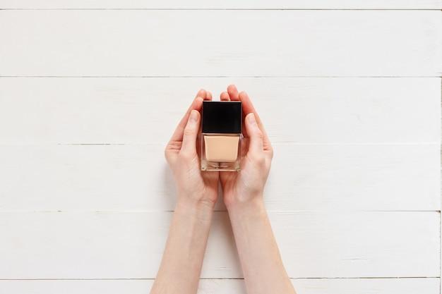 Base fluida com produto de maquiagem nas mãos da mulher.