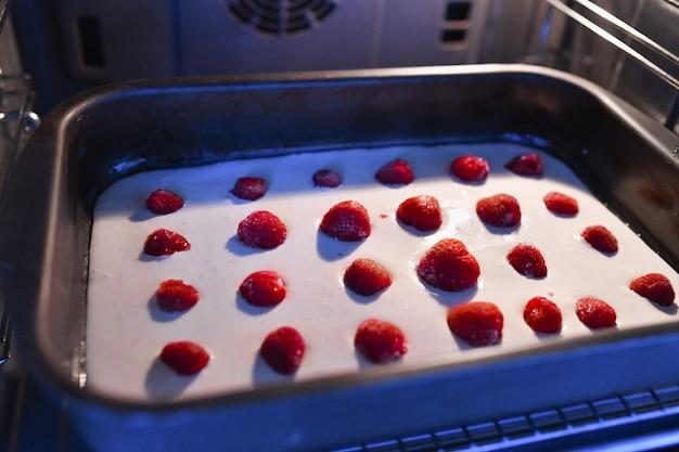Base para torta de morango no forno. torta ou torta de morango e banana fresca saudável com creme em uma crosta de torta dourada recém-assada, servida em uma assadeira e papel de forno