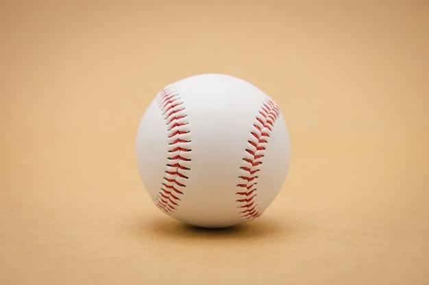Basebol isolado em um fundo marrom e basebol de costura vermelho. beisebol branco