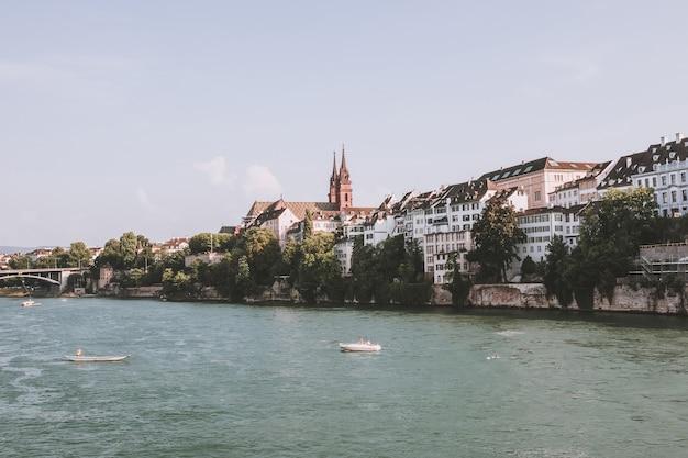 Basileia, suíça - 23 de junho de 2017: vista sobre a cidade de basileia e o rio reno. paisagem de verão, clima ensolarado, céu azul e dia ensolarado. pessoas nadam no rio