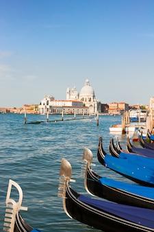 Basílica de santa maria della salute e gôndolas nas águas do grande canal, veneza, itália